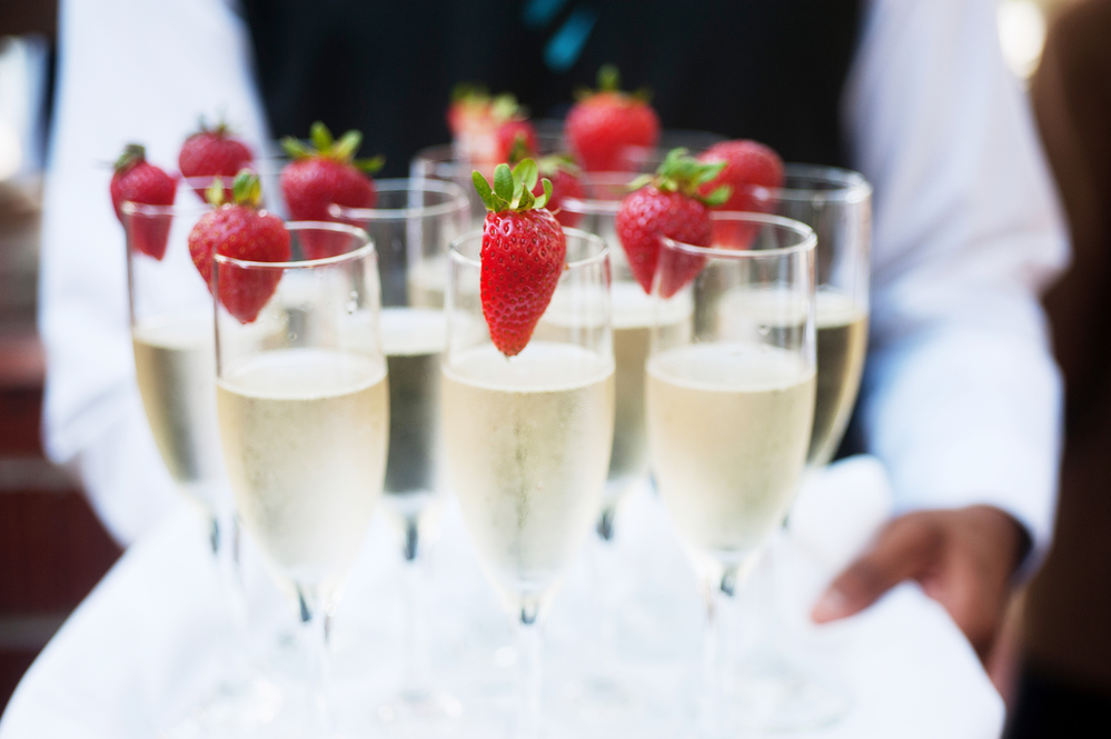 Waiter serving champagn with strawberries