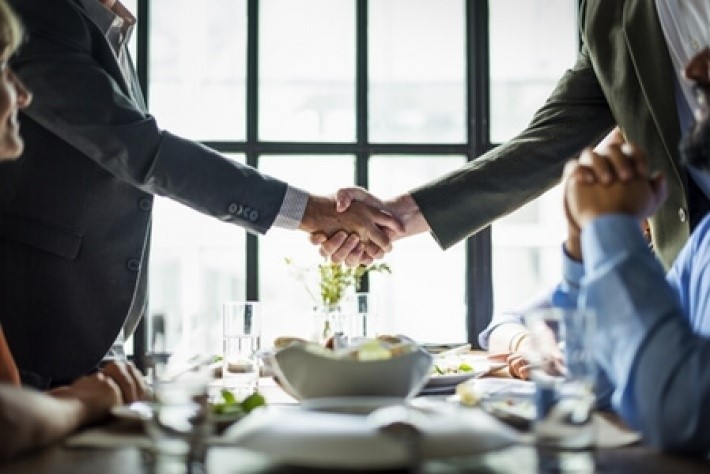 handshake over dinner table - what is corporate hospitality