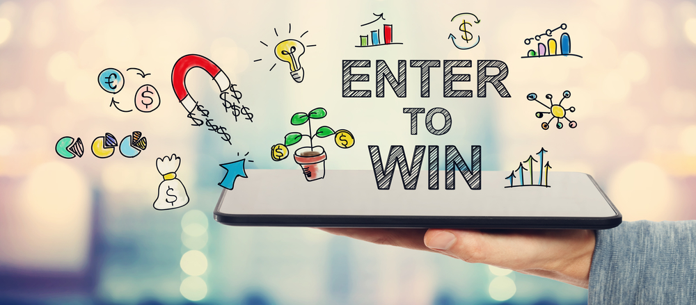 Enter To Win concept with man holding a tablet computer - social media competition ideas
